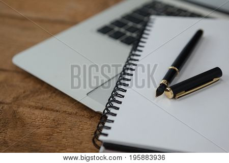 Close-up of laptop, pen, and diary on wooden background