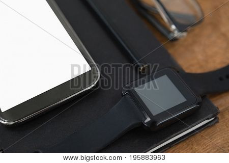 Close-up of diary, smart watch, pencil, smartphone and spectacles on wooden background