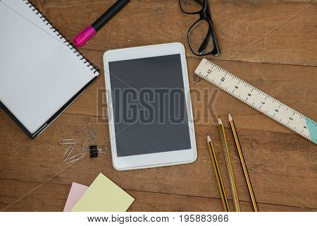 Overhead view of school supplies, digital tablet and spectacles on wooden table