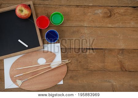 Slate, chalk, apple, watercolors, brush and water pallete on wooden background