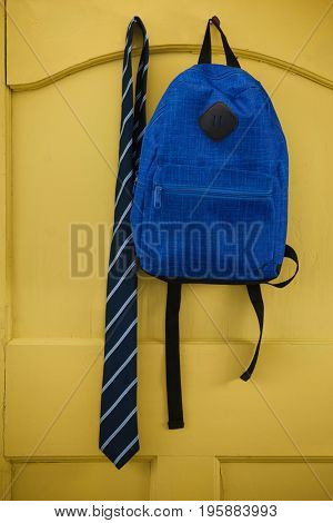 Schoolbag and tie hanging on yellow door