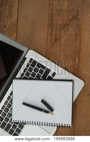 Top view of laptop, pen, and diary on wooden background