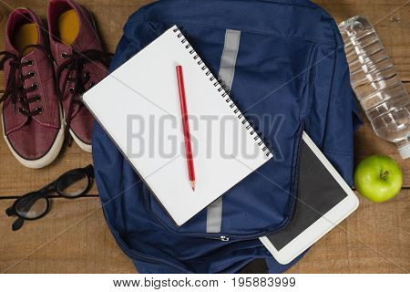 Bagpack, Diary, shoes, spectacles, digital tablet, apple and waterbottleagainst blue wooden background