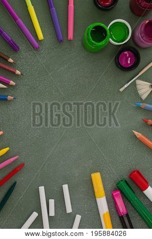 Overhead view of various drawing equipment arranged on chalkboard