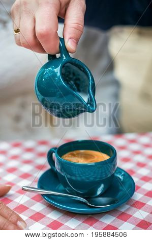 Pouring milk into coffee, a cup of coffee on the table