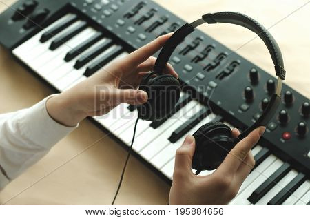 Woman in white shirt holds the headphones on the background of the synth. In the frame two hands.