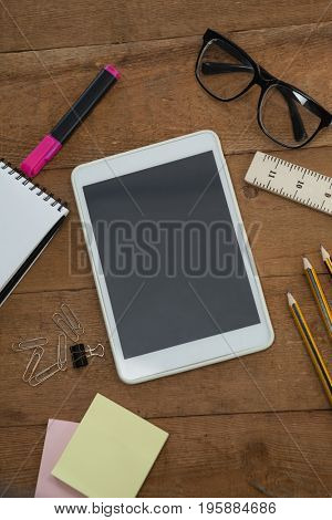 School supplies, digital tablet and spectacles arranged on wooden table