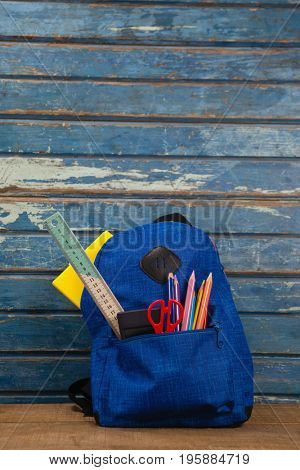 Various supplies in schoolbag on wooden table