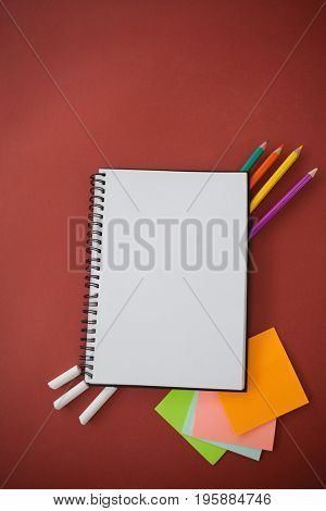 Overhead view of various school supplies arranged on red background