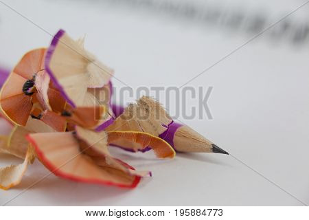 Close-up of pencil with pencil shavings on book