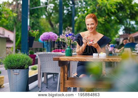 Portrait Of A Beautiful Intelligent Woman With Bright Red Hair. Stylish Young Girl In A Black Dress,