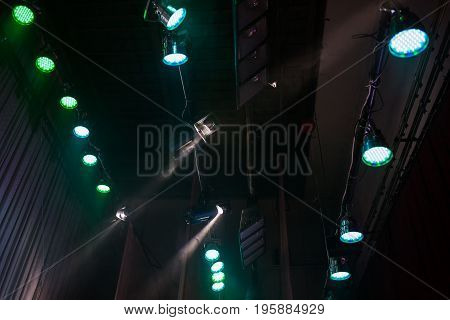 Color light in the concert stage. Color flood light on the ceiling. Soffits illuminate the scene. Electric light. Light equipment on stage for a concert. Color light at the concert. Spotlight with powerful light