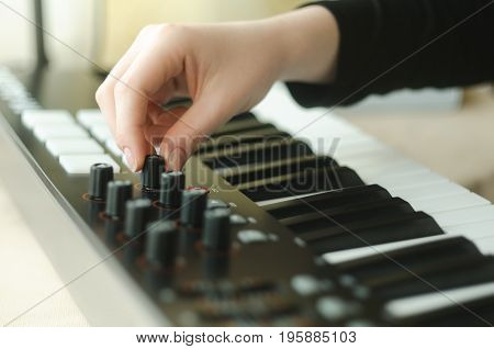 A woman in a black jacket adjusts the synthesizer. One hand in the frame. Side view
