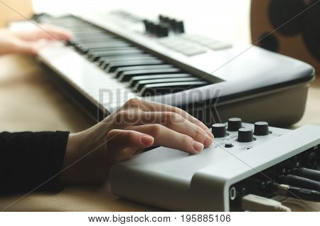 A woman in a black jacket adjusts the synthesizer on the music console while the other hand plays the synthesizer