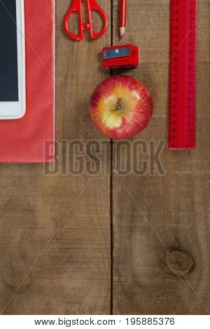 Overhead view of apple, digital tablet and school supplies on wooden table