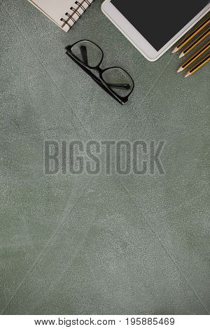 Overhead view of pencil, digital tablet, spectacles and book arranged on chalkboard