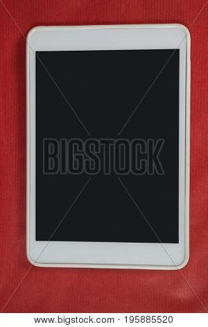 Close-up of digital tablet on red background