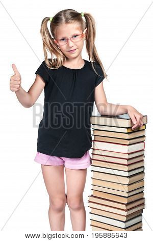 Beautiful schoolgirl with glasses showing thumb up leaning on a stack of books isolated on white background
