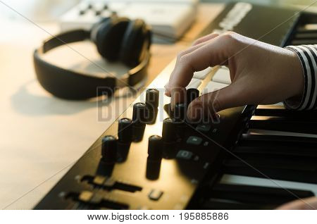 A woman in a shirt sets up a synthesizer. In the frame one hand. Nearby are headphones and a music console. Side view