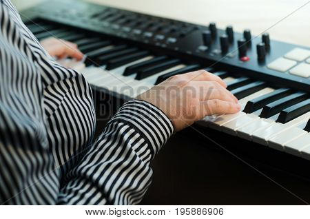 A woman in a striped shirt plays a synthesizer. In the frame the body. Side view. Light background