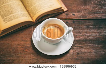Vintage Book And A Cup Of Coffee On Wooden Background