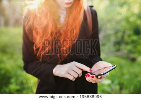 Red-haired stylish girl with mobile phone in the background of the setting sun. Retouch the photo on the phone. Dial on mobile gadget. Fashionable gadget. New gadget in female hands. Do selfie on a background of foliage on a mobile gadget.