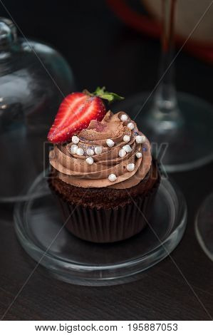 Chocolate cupcakes with strawberry on a glass stand.