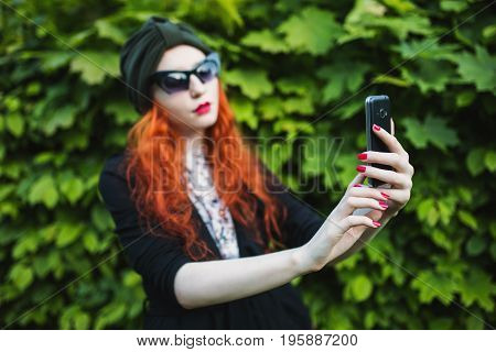 Red-haired stylish girl with a turban on her head and sunglasses with a mobile phone. Make selfies on mobile phone. Selfie concept on a background of foliage. Make selfi mobile cameras. The girl makes selfie. Fashionable selfie on a summer background