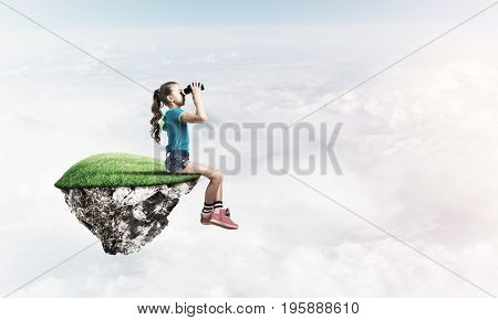 Cute young girl looking through binoculars sitting on floating island high in sky