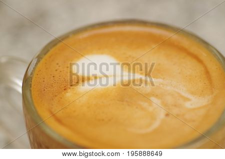 Close up of coffee cup with latte art on top in ablurred background.