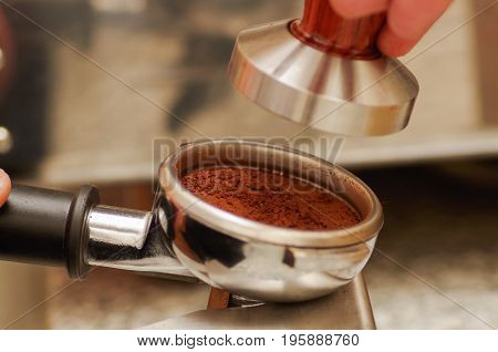 Close up of chocolate powder with cinnamon in a coffee strainer, in a blurred background.