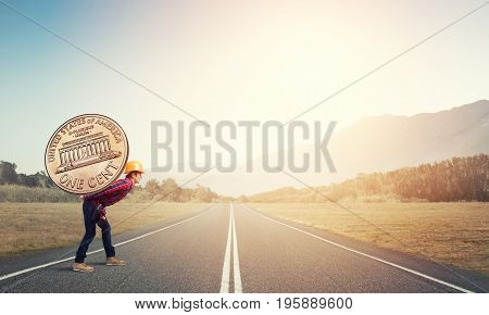 Builder man carrying on his back big cent coin crossing a highway