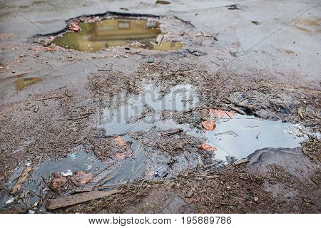 Old broken  road with rocks and puddles. Dirt on the road. A broken road. Broken asphalt. The old broken roadway