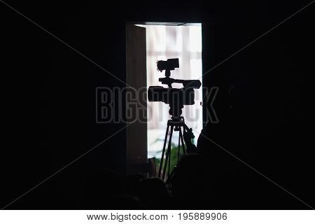 Camera on a black background. Capture a video. Creative work. To shoot a movie. Video equipment. Silhouette of a video camera. To shoot a video at a concert on the camera. A large video camera on the tip. Video reportage