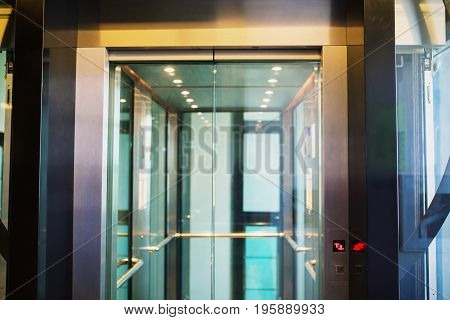 New elevator. A modern reliable elevator. Get down on the elevator. Transparent doors are closed in the elevator
