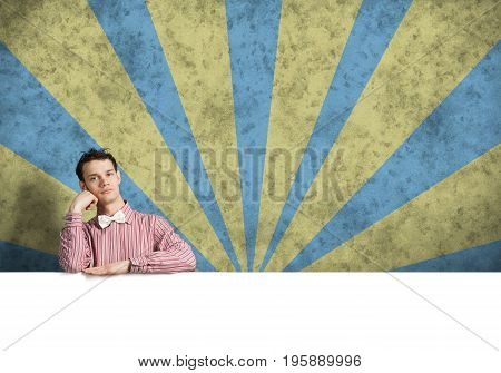 Young bored guy in checked shirt behind blank white banner