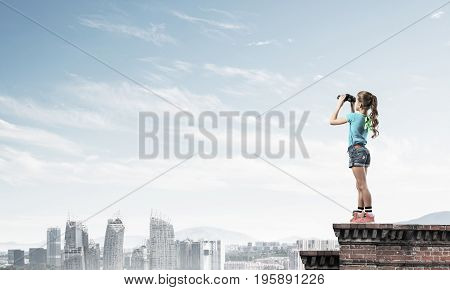 Cute girl of school age on building roof looking through binoculars