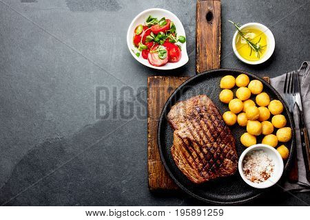 Grilled beef steak served on cast iron plate with tomato salad and potatoes balls. Barbecue, bbq meat beef tenderloin. Top view, slate background.