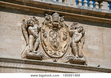 Detail of stone ornament of building in front of the Palace of the Popes of Avignon, under a sunny blue sky. Located in the Vaucluse department, Provence-Alpes-Côte d'Azur region, southeastern France