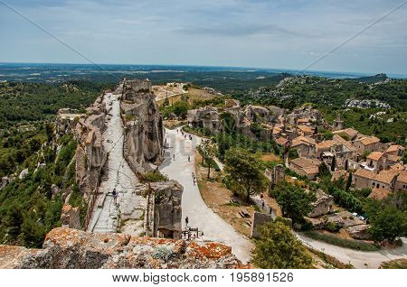 Panoramic view of the Baux-de-Provence castle ruins on the hill, with the roofs of the village just below. Vaucluse department, Provence-Alpes-Côte d'Azur region, southeastern France