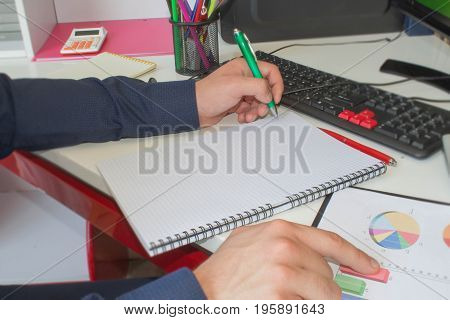 Man hand with pen calculator and computer on wooden table. Side view of man hands. He is using his calculator and writing numbers down. Concept of accounting work