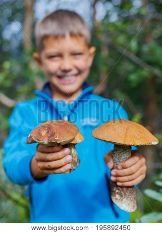 Portrait of cute boy with wild mushroom found in the forest. Focus on the mushroom