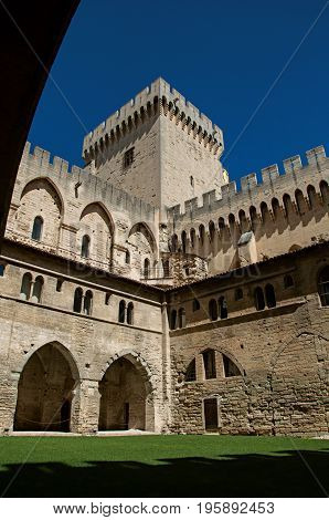 View of courtyard and internal buildings of the Palace of the Popes of Avignon, under a sunny blue sky. Located in the Vaucluse department, Provence-Alpes-Côte d'Azur region, southeastern France