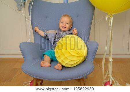 One year old baby boy first birthday. Toddler child sitting in chair and having fun with balloons
