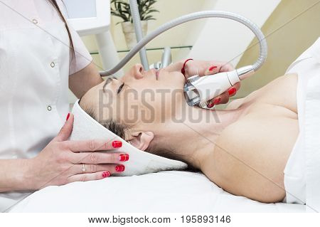 The procedure of lipomassage in a beauty salon makes a woman