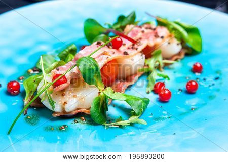 Salad with sea scallops, basil, bacon and cranberries on blue plate served in restaurant