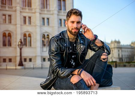 A handsome young hipster man sitting on the stairs on a square while talking on his smartphone