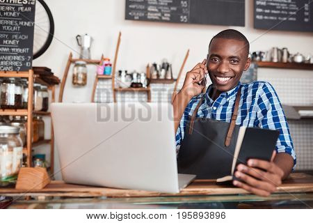 Smiling young African entrepreneur standing at the counter of his cafe talking on a cellphone and reading from a notebook while using a laptop