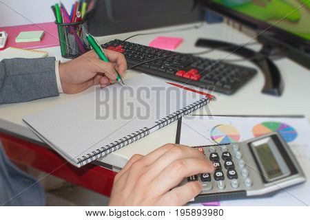 closeup pen on paperwork accounts with man use computer to save data in background. accounting concept. Man hand with pen calculator and computer on wooden table