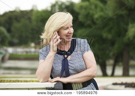 Happy old blonde calling by phone. Portrait of lovely middle aged woman in the summer park